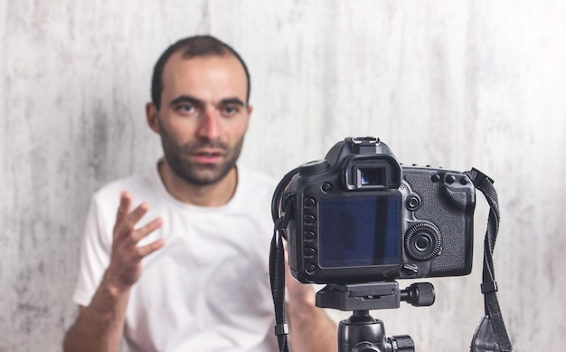 Kamera na statywie filmuje mężczyznę. blogger