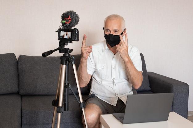 Kamera nagrywa blog wideo starszego męskiego blogera w masce w domu, blogowanie, videoblog i koncepcja ludzi