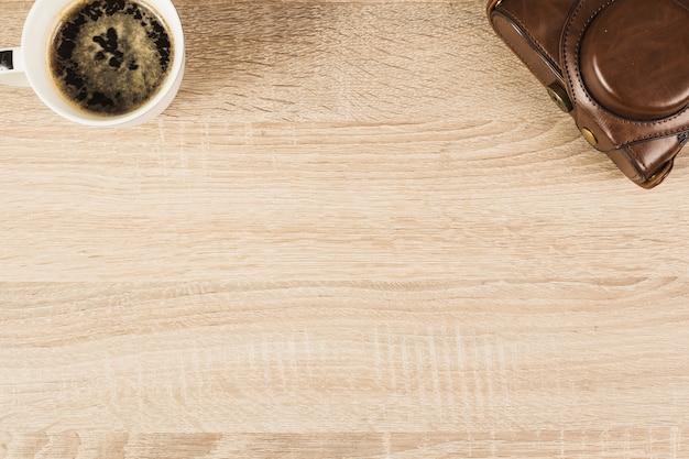 Kamera w saszetce i filiżance kawy na drewnianym stole