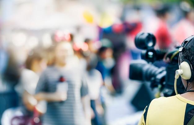 Kamera wideo mężczyzna pracujący na zewnątrz z młoda kobieta reporter.