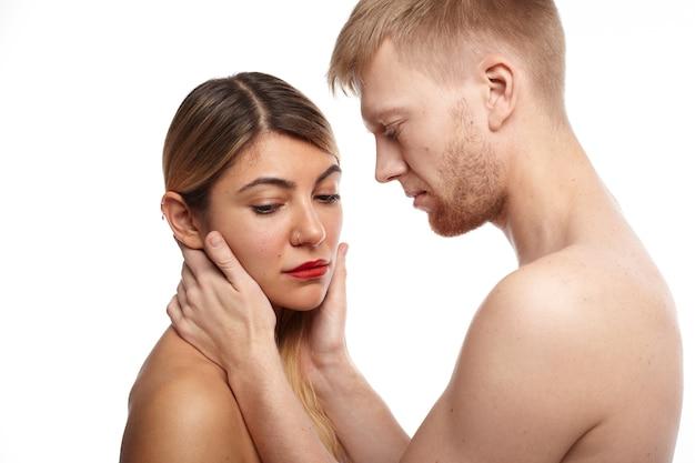 Kameralne zdjęcie pary dorosłej kobiety i mężczyzny bez ubrania. czuły kaukaski partnerzy uprawiający miłość: brodaty mężczyzna dotyka ładnej twarzy nieśmiałej blondynki, która patrzy w dół
