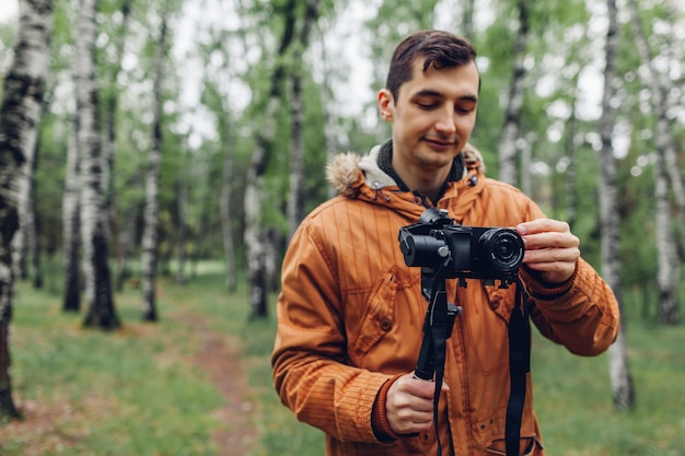 Kamerzysta filmujący wiosną las człowiek używający steadicamu i aparatu do robienia zdjęć