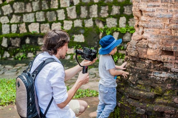 Kamerzysta i jego syn kręcą wideo w elektronicznym stabilizatorze steadycam aby nakręcić w po nagar cham tovers. koncepcja technologii cyfrowej.