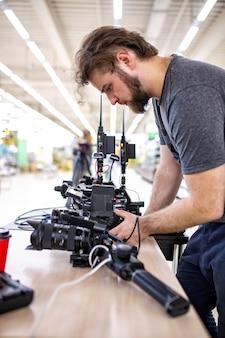 Kamerzysta kręci film lub program telewizyjny w studio za pomocą profesjonalnego aparatu, za kulisami