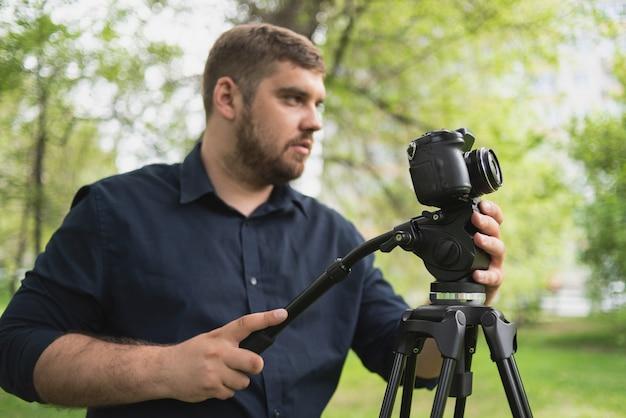 Kamerzysta kręci wideo w zielonym parku.