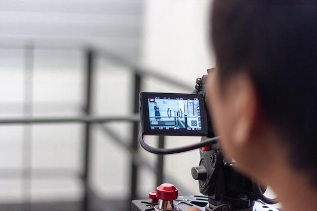 Kamerzysta pracujący przy produkcji wideo z aparatem fotograficznym