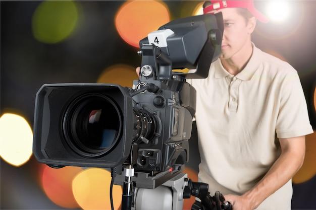 Kamerzysta pracujący z kamerą na białym tle