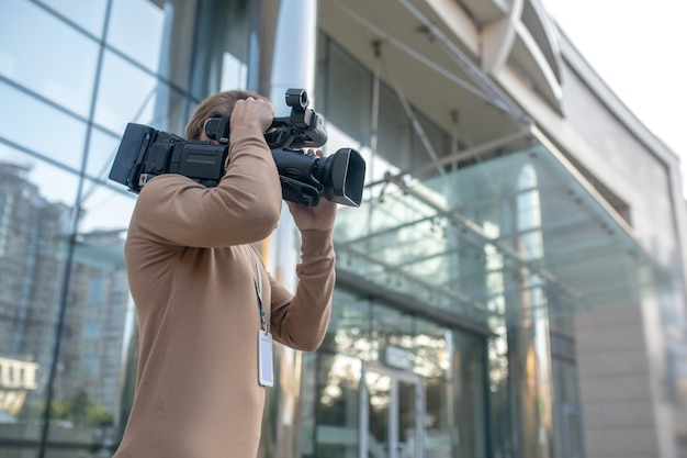 Kamerzysta trzymający aparat na ramieniu
