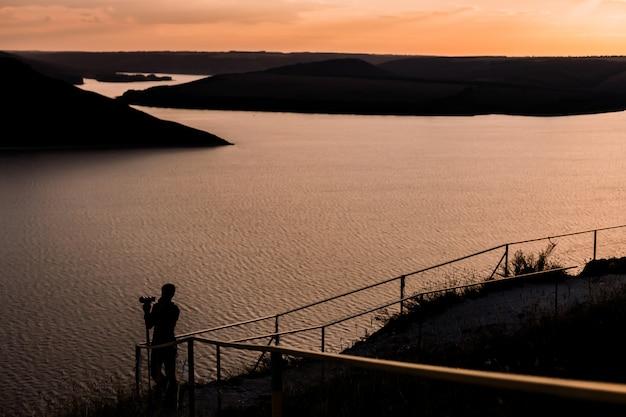 Kamerzysta z sylwetką aparatu dslr na jeziorze