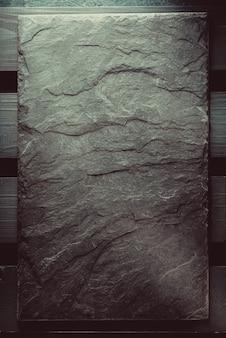 Kamień łupkowy na drewnianej teksturze tła
