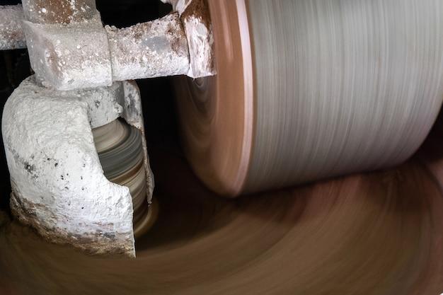 Kamień młyński przemysłowego melangera mielą i mieszają kakao i inne składniki w procesie wytwarzania czekolady, rozmytej w ruchu