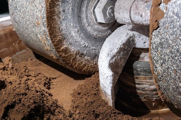 Kamień młyński przemysłowego melangera miele i miesza kakao i inne składniki w procesie produkcji czekolady, zbliżenie