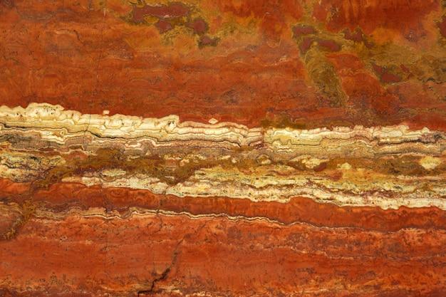 Kamień naturalny w kolorach bujnej lawy z białym paskiem o nazwie travertin rosso.