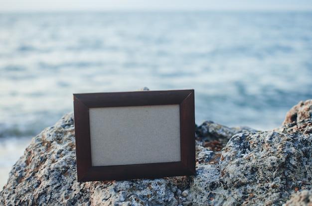 Kamień ramki na zdjęcia w lecie, morze w miejscu zachodu słońca