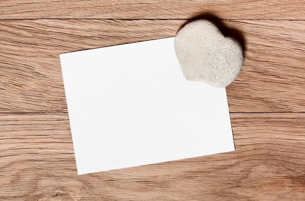 Kamień w kształcie serca i kawałek gratulacyjny na drewnianym tle