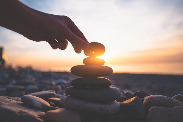 Kamień z dziurą o zachodzie słońca. znajdź talizman i złóż życzenie