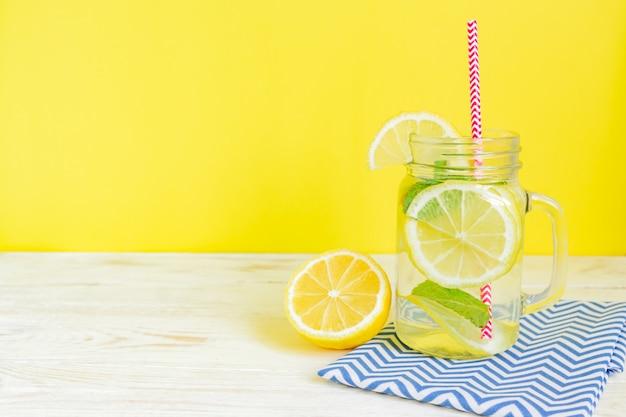 Kamieniarza słoju szkło domowej roboty lemoniada z cytrynami, mennicą i czerwieni papierową słomą na drewnianym nieociosanym tle ,. letni orzeźwiający napój.