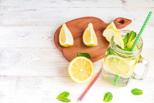 Kamieniarza słoju szkło domowej roboty lemoniada z cytrynami, mennicą i zielonego papieru słomą na drewnianym nieociosanym tle ,. letni orzeźwiający napój.