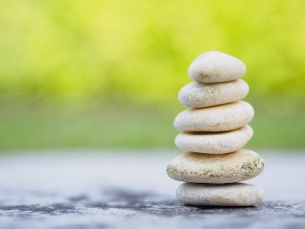 Kamienie balansowe ułożone na piramidzie w miękkim zielonym tle.