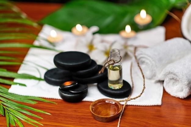Kamienie do kamienia terapeutycznego znajdujące się na ręczniku frotte, obok których znajdują się świece i butelki z aromatycznym olejem oraz pojemnik na olej i gałązkę kwiatów