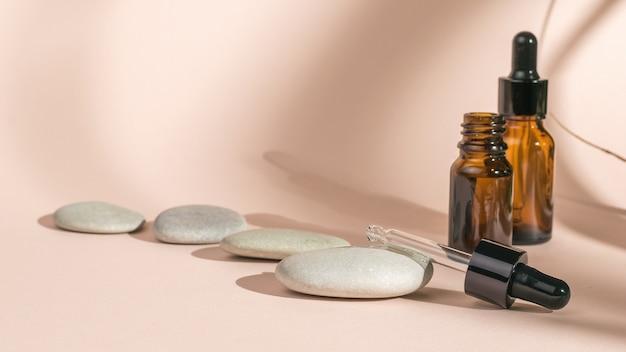 Kamienie i butelki medyczne na beżowym tle w cieniu roślin.