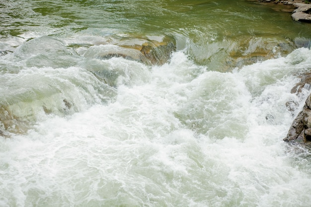 Kamienie i górska rzeka z małym wodospadem