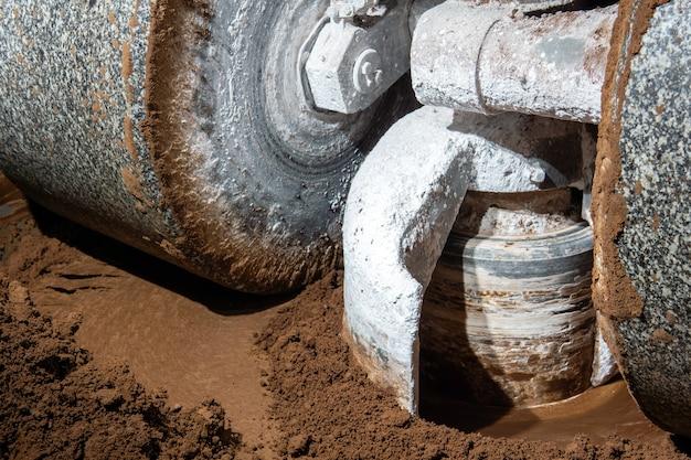 Kamienie młyńskie przemysłowego melangera mielą i mieszają kakao i inne składniki w procesie produkcji czekolady, zbliżenie