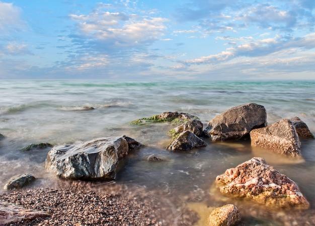 Kamienie morskie, kamyki, niebo z chmurami
