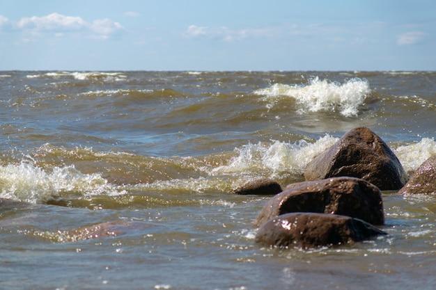 Kamienie na plaży morskiej myte przez fale w słoneczny letni dzień