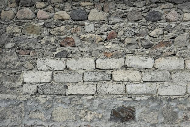 Kamienie o różnych rozmiarach i kształtach leżą jeden na drugim. cement między nimi. t