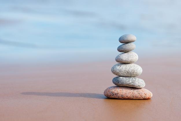 Kamienie piramidy balansują na piasku plaży. obiekt jest ostry, zamazany.