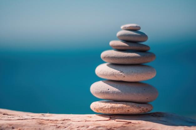 Kamienie piramidy nad brzegiem morza w słoneczny dzień na tle błękitnego morza wesołych świąt żwirowa plaża