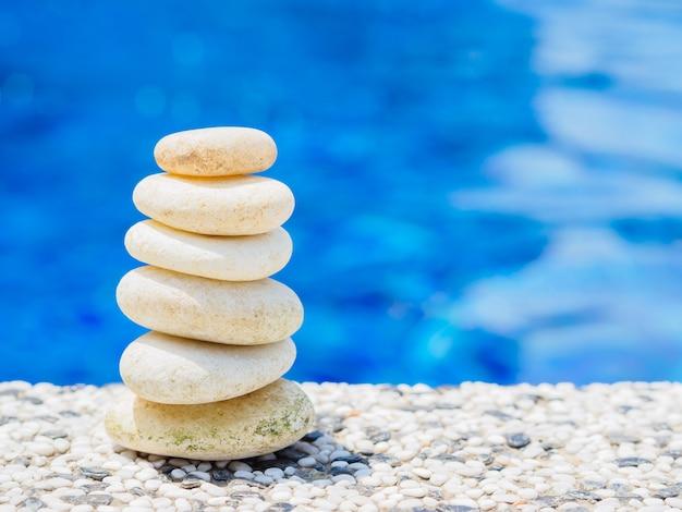 Kamienie równowagi ułożone w piramidę na miękkim niebieskim tle wody