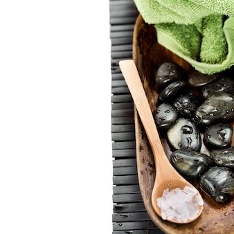 Kamienie spa w drewnianej misce i sól na łyżce