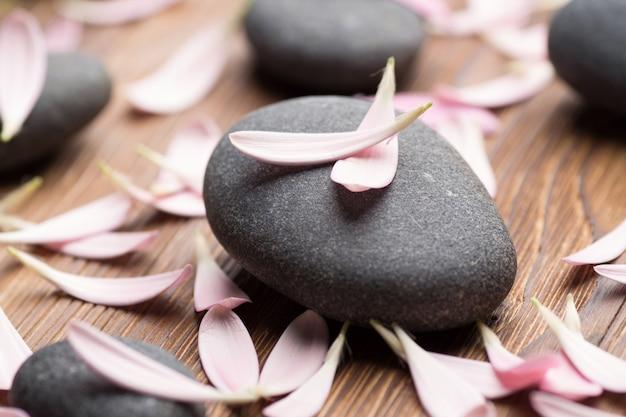 Kamienie spa z płatkami kwiatów. masaż relaksacyjny.