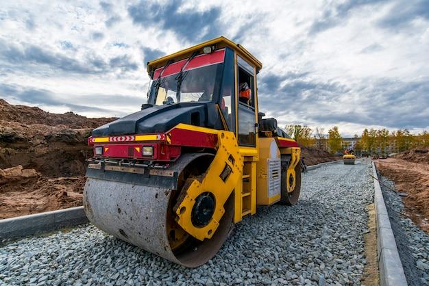 Kamienie ubijające wałek traktorowy do nowej drogi w budowie