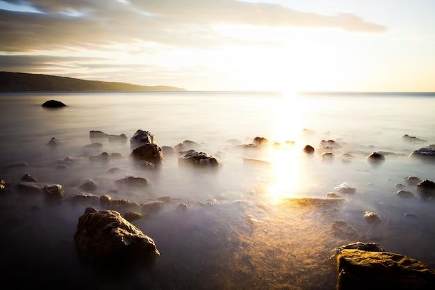 Kamienie w oceanie przed zachodem słońca, nad którym mgła. niebo jest wypełnione chmurami. daleko za horyzontem są góry