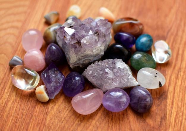 Kamienie w różnych kolorach. ametyst, kwarc różowy, agat, apatyt, awenturyn, oliwin, turkus, akwamaryn, kryształ górski na drewnianym tle