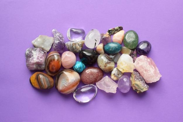 Kamienie w różnych kolorach. ametyst, kwarc różowy, agat, apatyt, awenturyn, oliwin, turkus, akwamaryn, kryształ górski na fioletowym tle