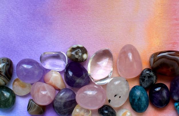 Kamienie w różnych kolorach. ametyst, kwarc różowy, agat, apatyt, awenturyn, oliwin, turkus, akwamaryn, kryształ górski na tle tęczy