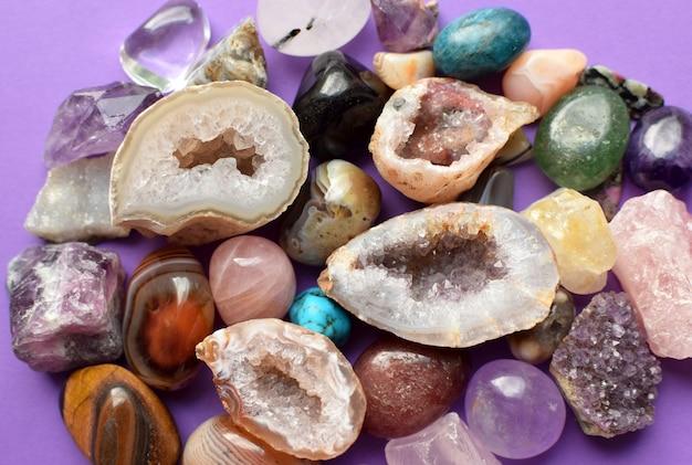 Kamienie w różnych kolorach. geoda ametyst, kwarc różowy, agat, apatyt, awenturyn, oliwin, turkus, akwamaryn, kryształ górski na fioletowym tle