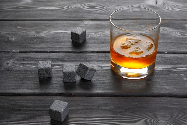 Kamienie whisky i whisky na drewnianym stole