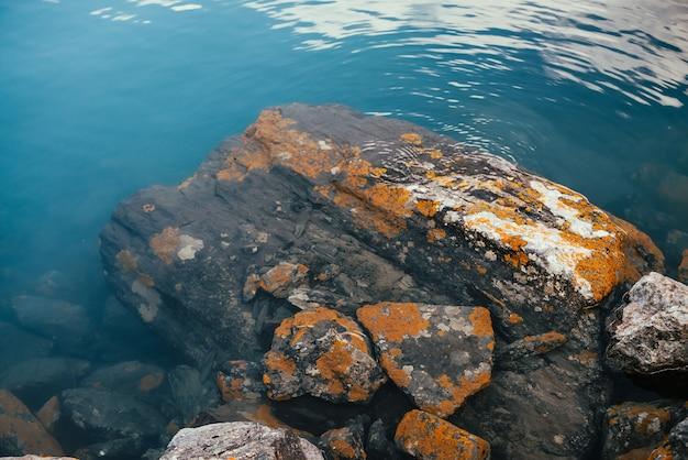 Kamienie z pomarańczowymi porostami w lazurowej spokojnej wodzie z bliska górskiego jeziora. klimatyczna przyroda, turkusowe jezioro z porostami i głazami.
