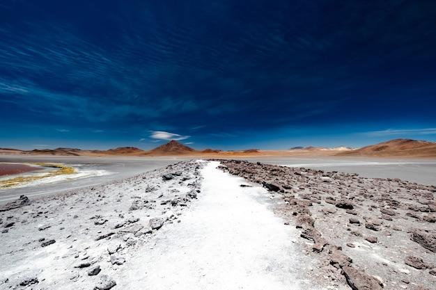 Kamienista droga wśród szerokiej górskiej pustyni boliwijskiej