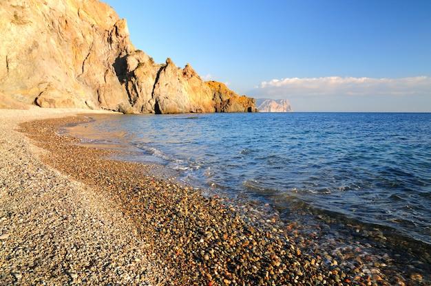 Kamienista plaża jest obmywana przez spokojne fale morskie