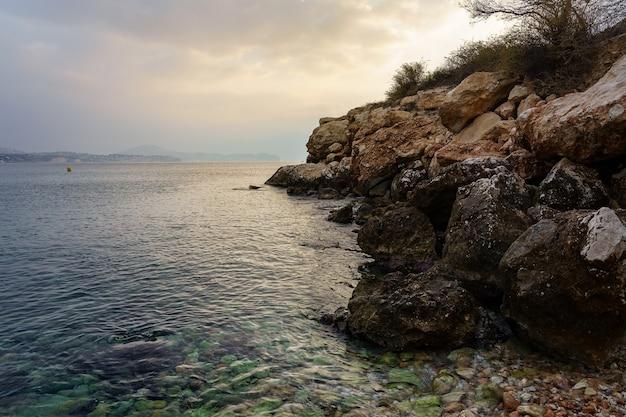 Kamienista plaża obok skał klifowych na złoty zachód słońca.