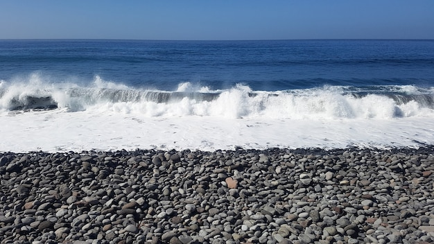 Kamienista plaża z falami oceanu, brak ludzi, wolność i spokój pod błękitnym niebem