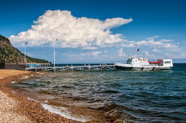 Kamienisty brzeg i statek przy molem w słonecznym dniu i chmurze