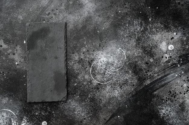 Kamienna deska do krojenia pusty zestaw z kopią miejsca na tekst lub jedzenie z kopią miejsca na tekst lub jedzenie, widok z góry płasko leżał, na czarnym tle ciemnego kamiennego stołu
