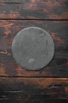Kamienna deska do krojenia pusty zestaw z kopią miejsca na tekst lub jedzenie z kopią miejsca na tekst lub jedzenie, widok z góry płasko leżał, na starym ciemnym drewnianym stole tło